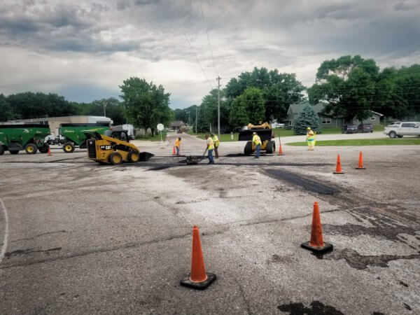 Workers close off an area of highway to perform crack repair in Sioux County.