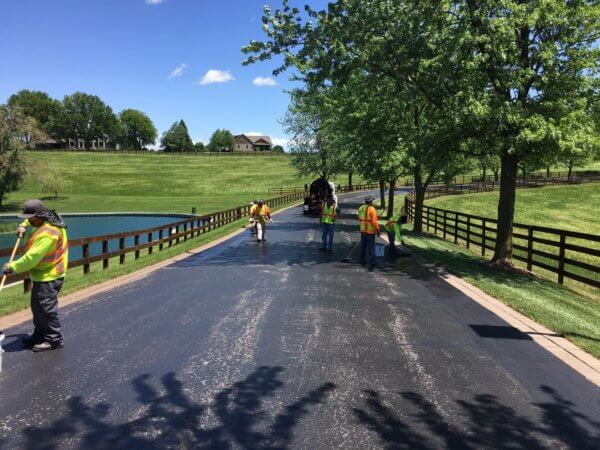 Workers spray and prepare an asphalt driveway for resurfacing.