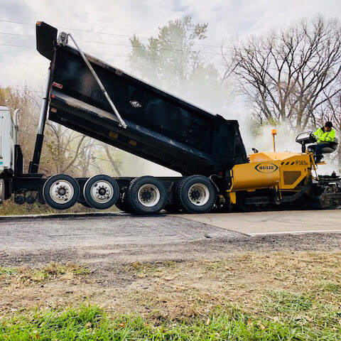 New asphalt surface material is installed using one lift of a dump truck.
