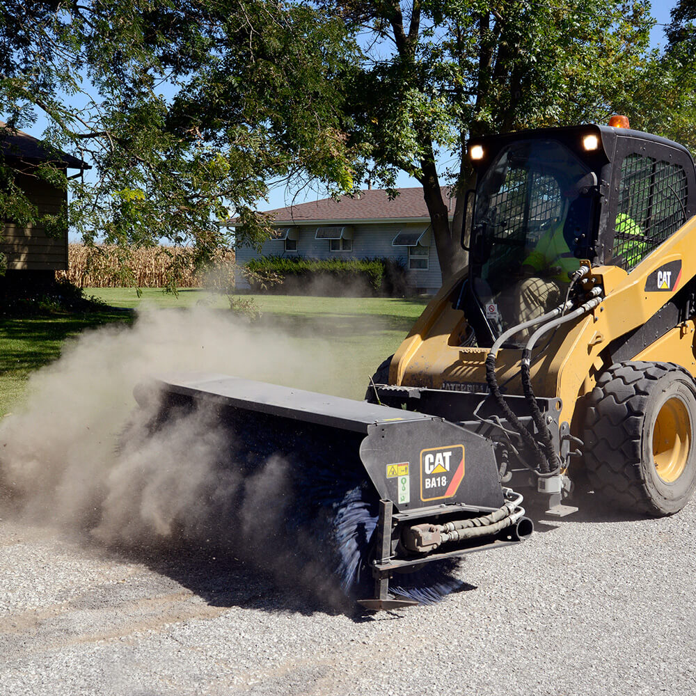 Pavement surface is swept with a power broom.