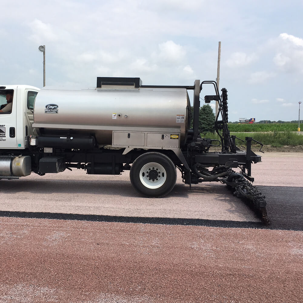 Binder is applied at a specific rate by a truck.