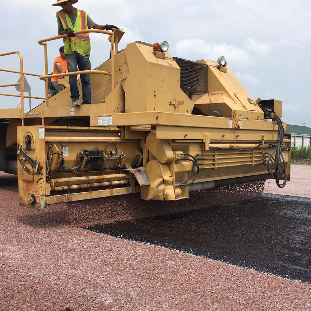 Cover aggregate is applied during a chip sealing job.