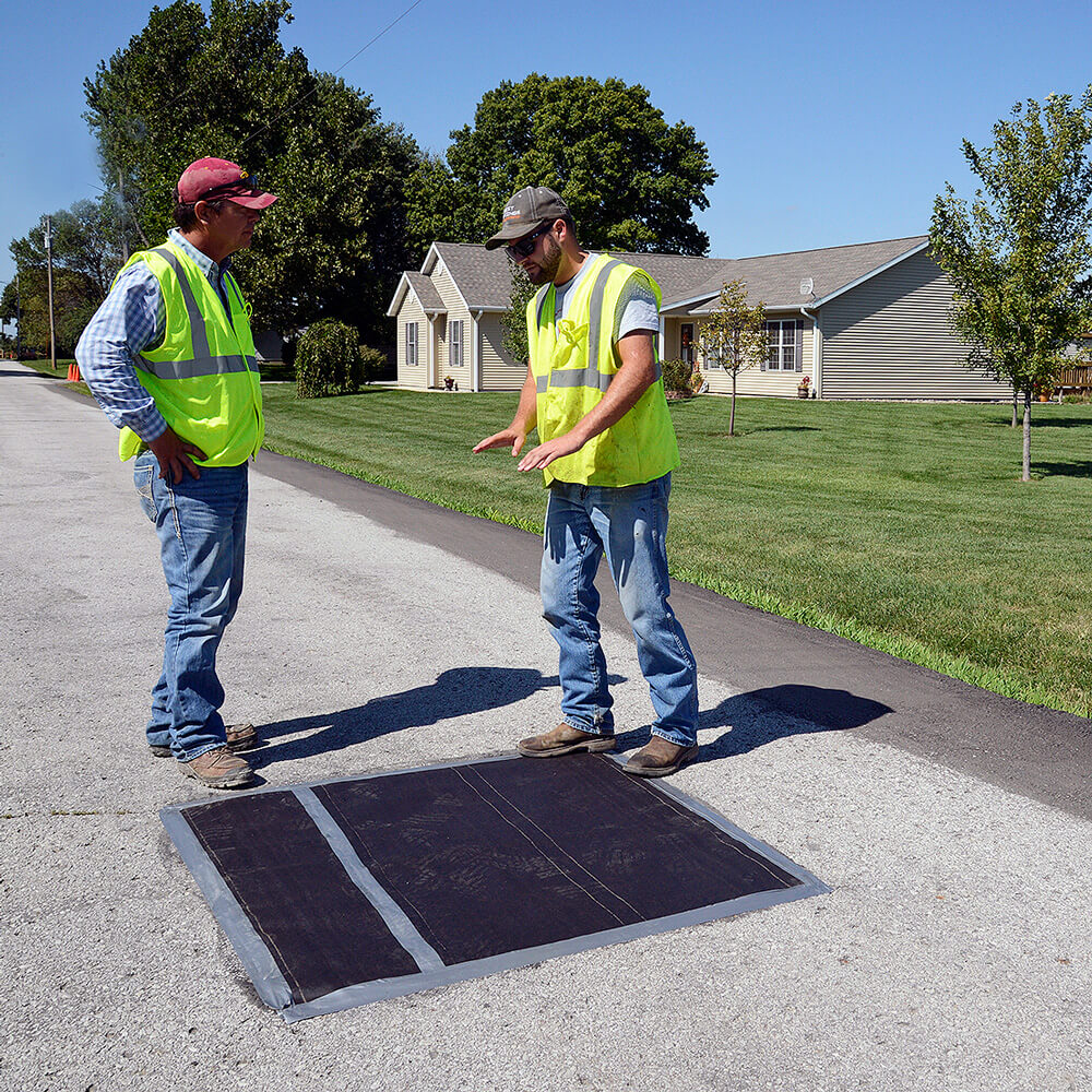 Two MWC crew members cover manholes and water valves.