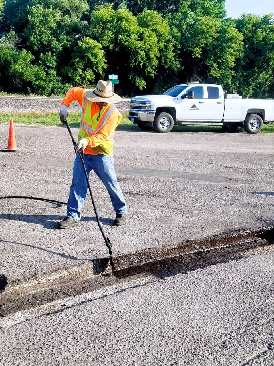 A midwest coatings worker uses a long tool to spread asphalt across a crac.