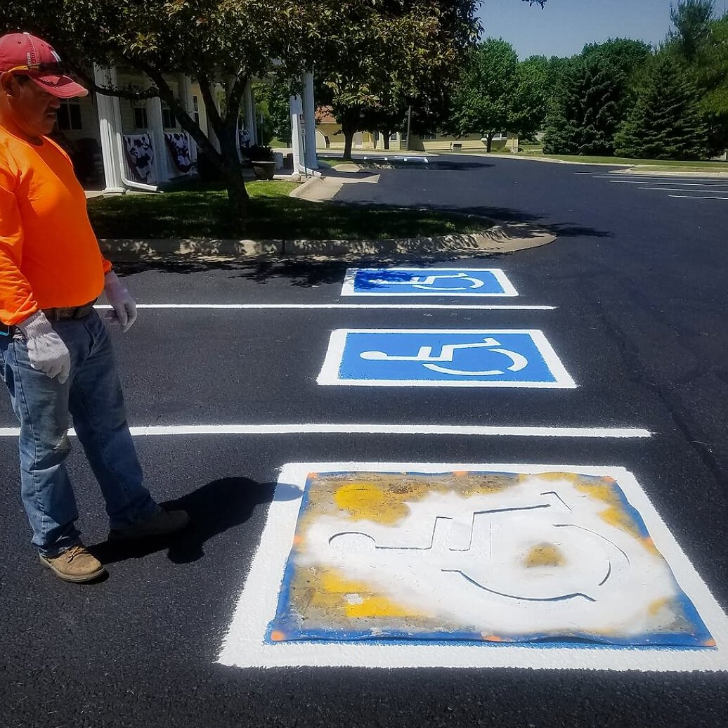 A photo of a worker viewing some seal coating work on a handicap parking space.