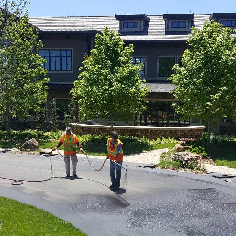 Workers work together with a sprayer to apply seal coating on an asphalt driveway.