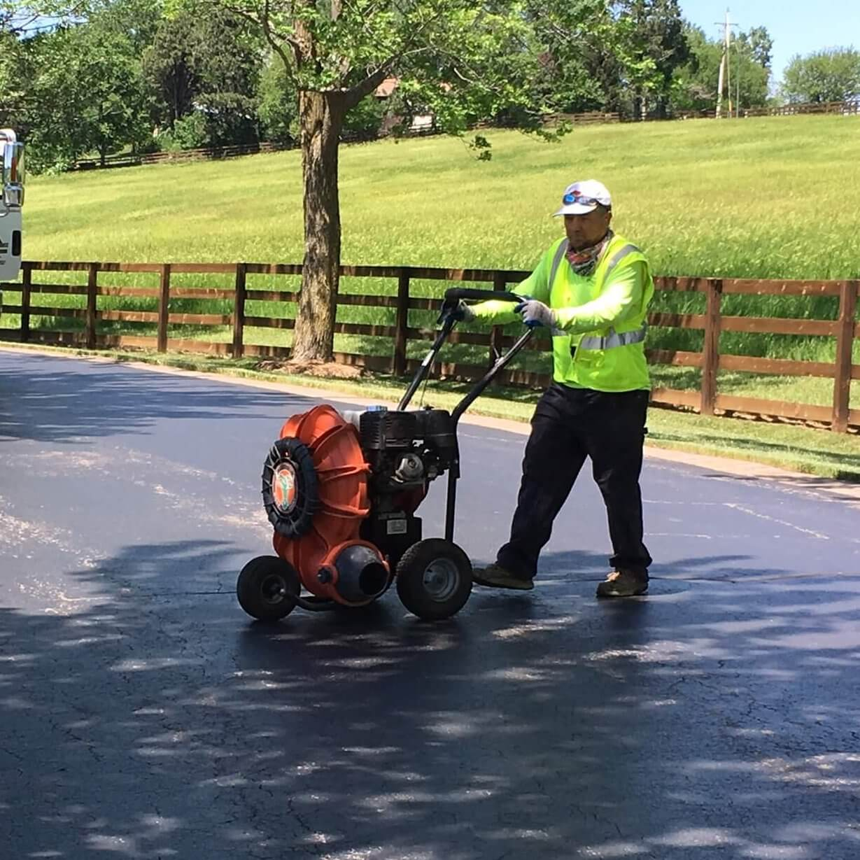 Midwest Coatings worker pushes equipment along a driveway to perform a sealcoating job.